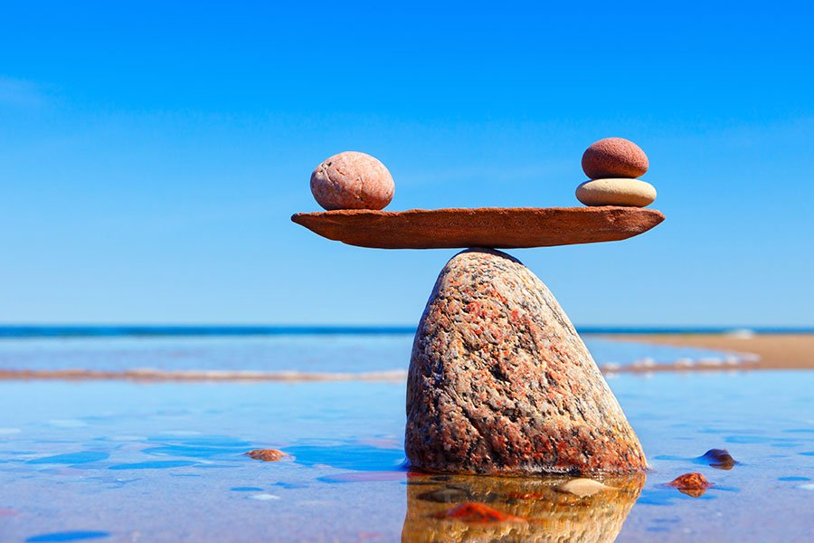 stones balancing on top of another stone on a beach